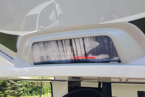 Defective fifth wheel hitch trailer backup mirror located on the front cap of a Keystone Montana.